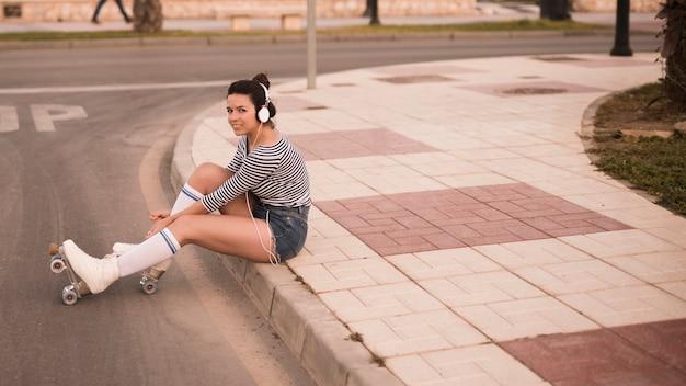 Musica d'ascolto della giovane donna sulla cuffia che si rilassa sulla strada Foto Gratuite