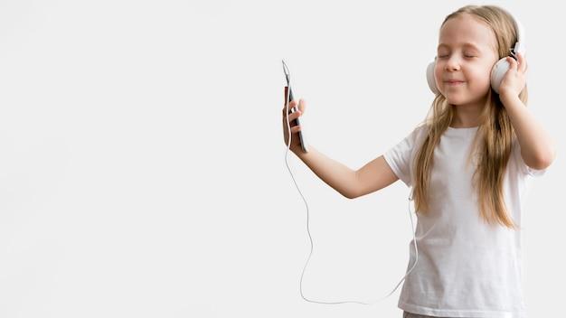 Musica d'ascolto della ragazza al cellulare con le cuffie Foto Gratuite