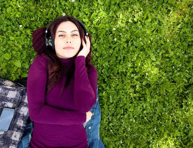 Musica d'ascolto sveglia della giovane donna con le cuffie Foto Premium