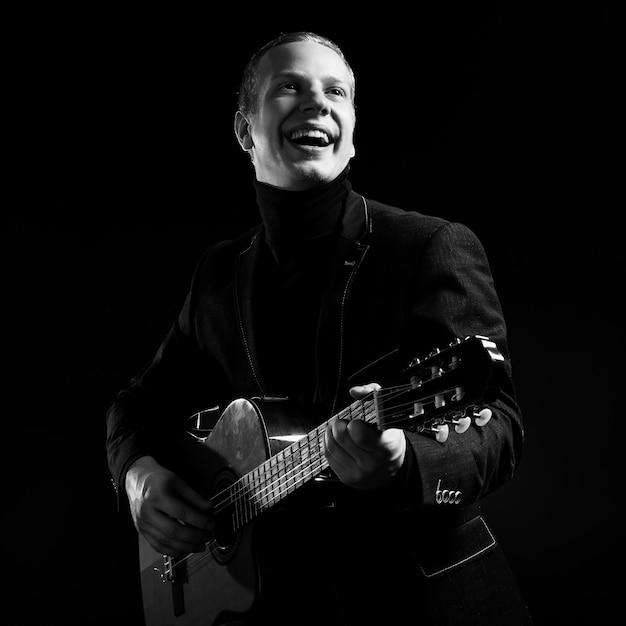 Musica. giovane musicista in abito nero in possesso di una chitarra Foto Gratuite