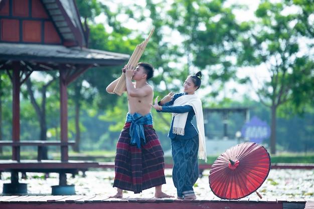 Musica thailandese, donne danzanti e uomo in costume in stile nazionale: danza thailandese Foto Gratuite
