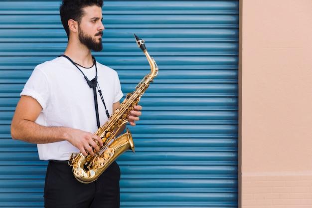 Musicista di colpo medio lateralmente che posa con il sassofono Foto Gratuite