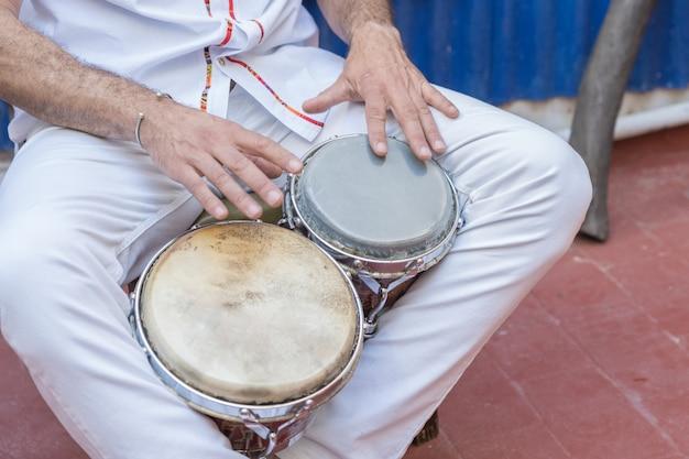 Musicista di salsa che suona i bonghi, uno strumento a percussione tradizionale per la musica caraibica e latinoamericana Foto Premium