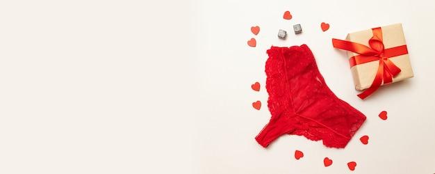 Mutandine di pizzo rosso con una confezione regalo a sorpresa avvolta in carta artigianale Foto Premium