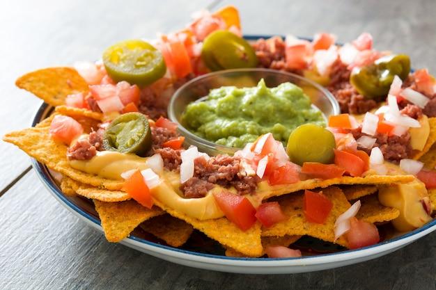 Nachos messicani con manzo, guacamole, salsa di formaggio, peperoni, pomodoro e cipolla nel piatto sul tavolo di legno Foto Premium