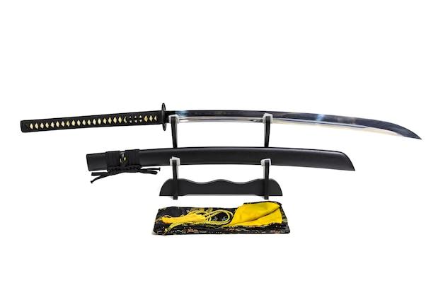 Nagamaki, spada giapponese a manico lungo con fodero nero su supporto in legno e borsa di seta Foto Premium