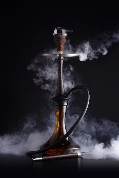 Narghilè alla moda con nuvola di fumo su sfondo nero Foto Premium