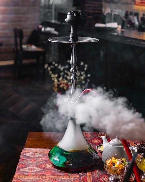 Narghilé di cottura a vapore verde sulla vista laterale del tè della tavola Foto Gratuite