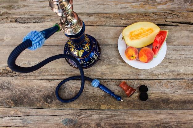 Narghilè, frutta, bacche su fondo in legno vecchio. Foto Premium
