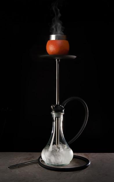 Narghilè moderno con ciotola di vetro e aroma di pompelmo su sfondo nero Foto Premium