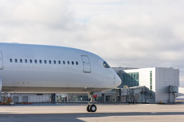 Naso e fusoliera con finestre dell'aeroplano sullo sfondo del terminal dell'aeroporto. Foto Premium
