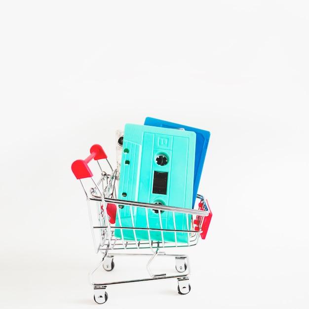 Nastri a cassetta del turchese e del blu in carrello di acquisto isolato sopra priorità bassa bianca Foto Gratuite