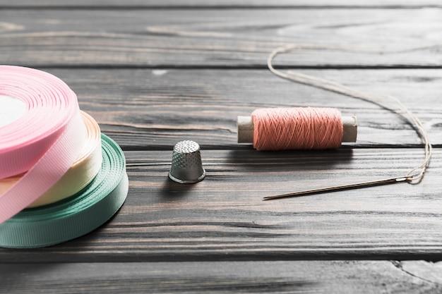 Nastri colorati rotolati e oggetti da cucire sul tavolo di legno Foto Gratuite