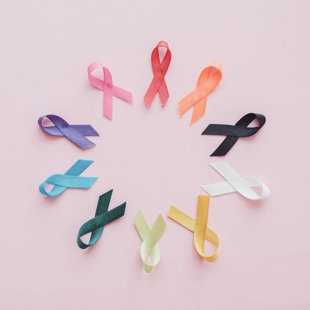 Nastri colorati su sfondo rosa, consapevolezza del cancro Foto Premium