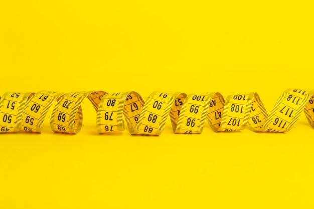 Nastro di misurazione su uno sfondo giallo. nastro di misurazione a forma di spirale attorcigliata su uno sfondo giallo. concetto di dimagrimento e dieta, copia spazio Foto Premium