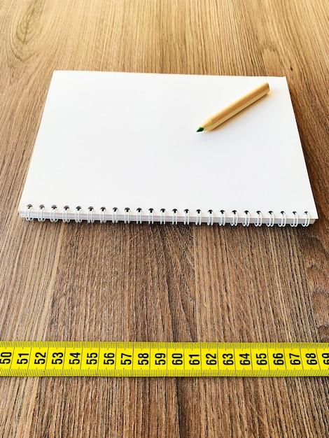 Nastro di misurazione sulla tavola di legno con il blocco note del diario del libro Foto Premium