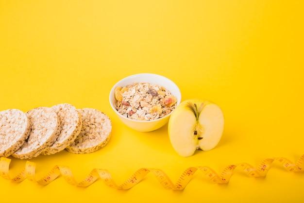 Nastro di misurazione vicino a frutta, pane fresco e ciotola di muesli Foto Gratuite