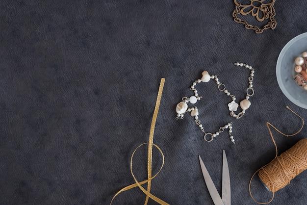 Nastro dorato; braccialetto; forbice; rocchetto di filo su sfondo nero con texture Foto Gratuite