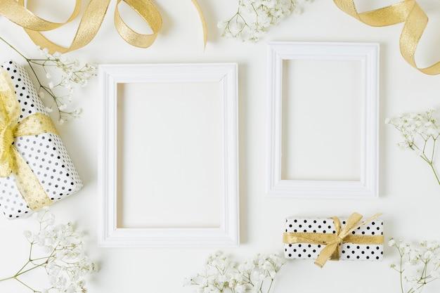 Nastro dorato; scatole da regalo; fiori del baby-breath vicino al telaio in legno su sfondo bianco Foto Gratuite