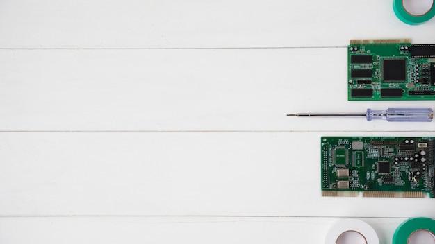 Nastro isolante; tester e circuito stampato sulla scrivania in legno bianco Foto Gratuite