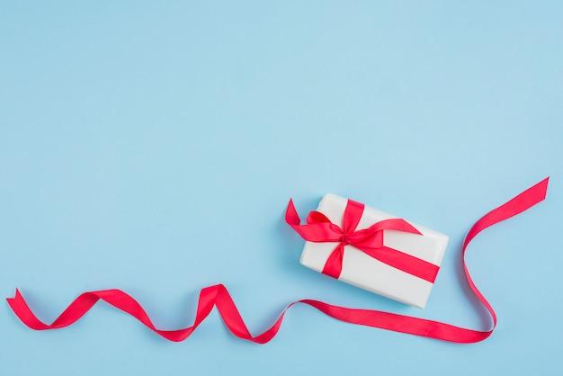 Nastro rosso vicino confezione regalo Foto Gratuite