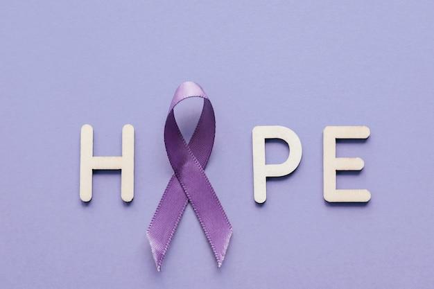 Nastro viola con la lettera di legno di speranza su priorità bassa viola Foto Premium