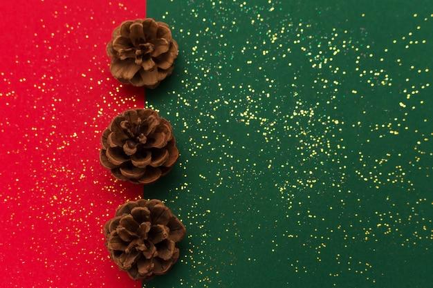 Natale con pigne e glitter scintillanti d'oro su sfondo verde e rosso tradizionale. Foto Premium
