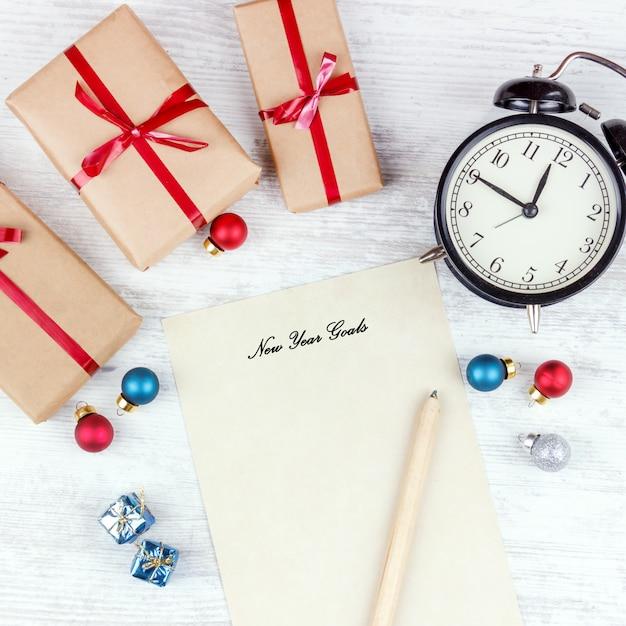 Natale con scatole regalo, sveglia, palle di decorazione di natale e foglio di carta sul tavolo di legno bianco Foto Premium