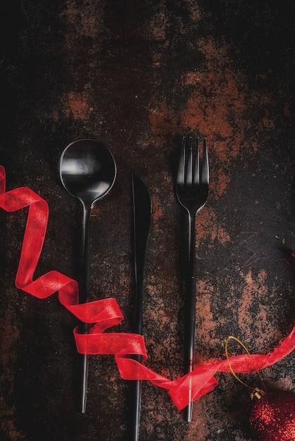 Natale, concetto di celebrazione del nuovo anno, set di argenteria su un arrugginito scuro, decorato con nastro rosso e palla dell'albero di natale, vista dall'alto copyspace Foto Premium