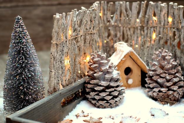 Natale decorazione-close up birdhouse, coni e recinzione con lampadine. Foto Premium