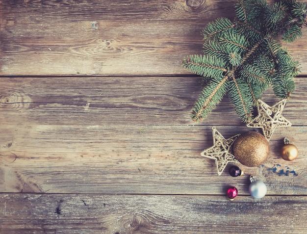 Natale o capodanno in legno rustico con decorazioni giocattolo e ramo di un albero di pelliccia, vista dall'alto Foto Premium