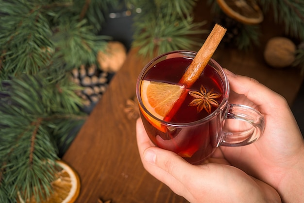 Natale vin brulé in un bicchiere nelle mani di un uomo con fette d'arancia a base di vino rosso con bastoncini di cannella piccanti Foto Premium
