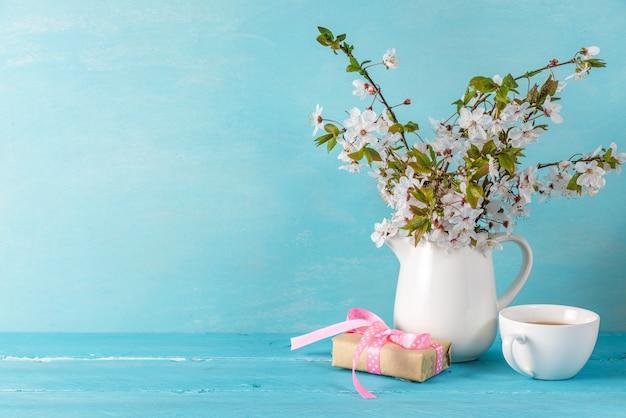 Natura morta con fiori di una bella primavera fiori di ciliegio, tazza di caffè e confezione regalo sul tavolo di legno blu con spazio di copia Foto Premium