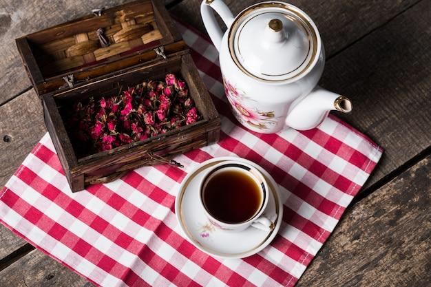 Natura morta con la tazza e la tovaglia di tè sulla tavola di legno Foto Premium