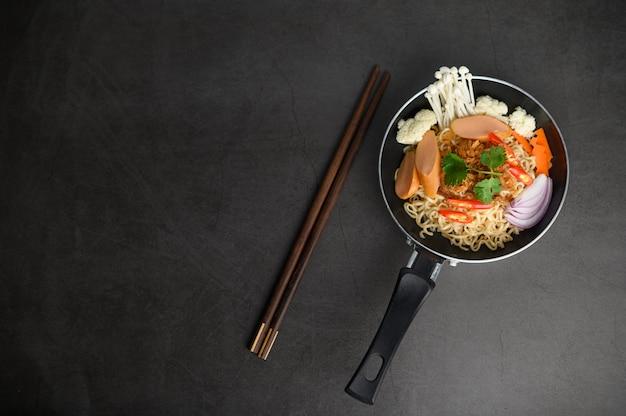 Natura morta con noodles in padella e bacchette. Foto Gratuite