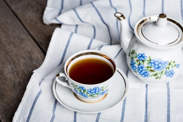 Natura morta con tazza di tè e tovaglia sul tavolo di legno Foto Premium