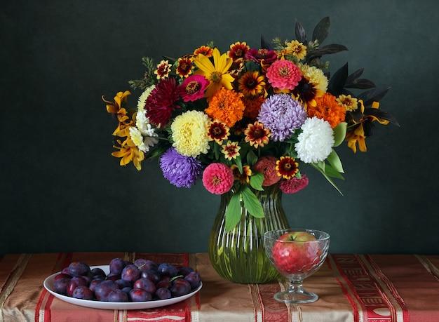 Natura morta con un bouquet di fiori autunnali, mele e prugne. Foto Premium