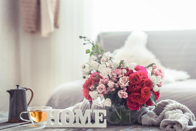 Natura morta con un'iscrizione a casa e un vaso di fiori Foto Gratuite