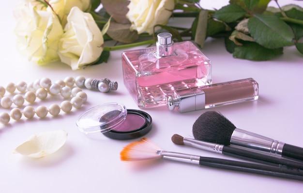 Natura morta degli oggetti della donna di modo su bianco. concetto di trucco femminile. rose bianche, profumo e ombra rosa, rossetto, perle Foto Premium