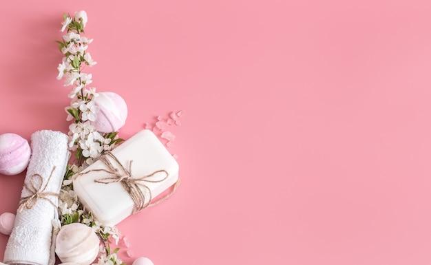 Natura morta della stazione termale su fondo rosa con i fiori della molla Foto Gratuite