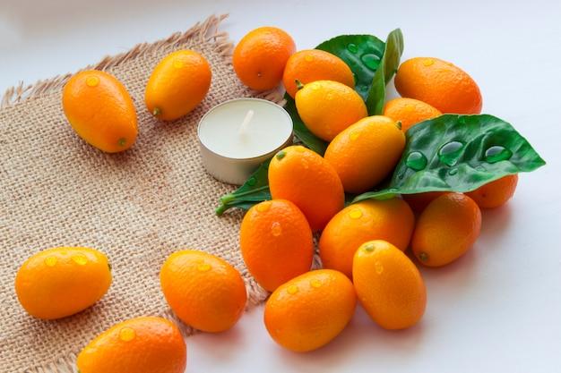 Natura morta di kumquat e candele su tela di sacco. sfondo rilassante. sfondo per il design spa. Foto Premium