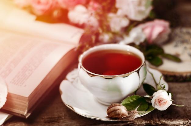 Natura morta vintage con una vecchia tazza da tè in porcellana, rosa fresca, lumaca e libro. Foto Premium