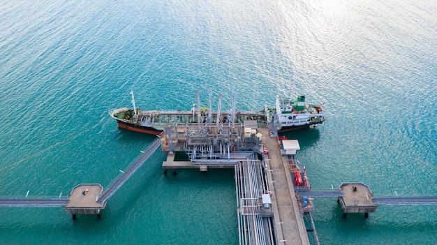 Nave cisterna di vista aerea che scarica al porto, olio dell'esportazione dell'importazione di affari con l'olio del trasporto della nave di autocisterna dalla raffineria sul mare. Foto Premium