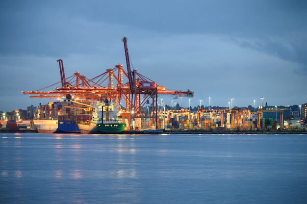 Nave mercantile internazionale con container cargo illuminata e gru a cavalletto nel porto Foto Premium