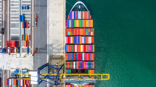 Nave porta-container che carica e che scarica nel porto marittimo profondo, vista superiore aerea dell'importazione e dell'esportazione logistiche di affari Foto Premium
