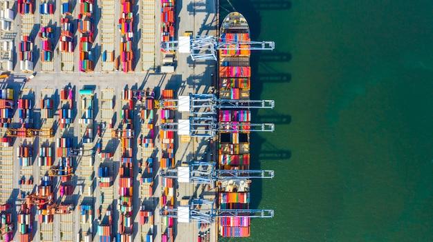 Nave porta-container che carica e che scarica nel porto marittimo profondo, vista superiore aerea dell'importazione logistica di affari ed esportazione del trasporto merci Foto Premium