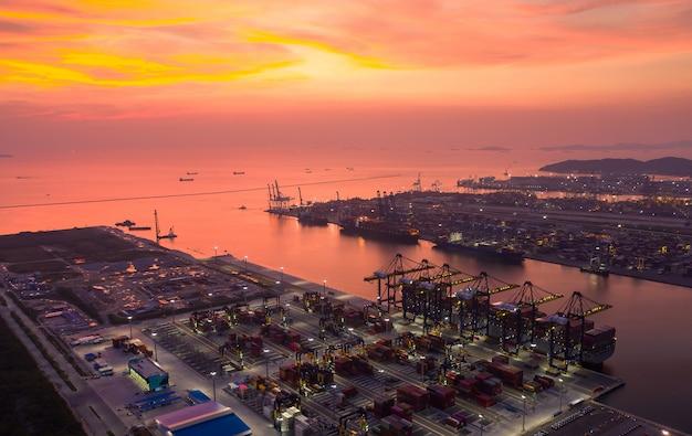 Nave porta-container di vista aerea a porto marittimo al tramonto Foto Premium
