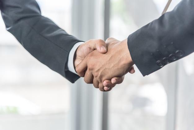 Negoziare gli affari, gli uomini d'affari si stringono la mano sul posto di lavoro. Foto Premium