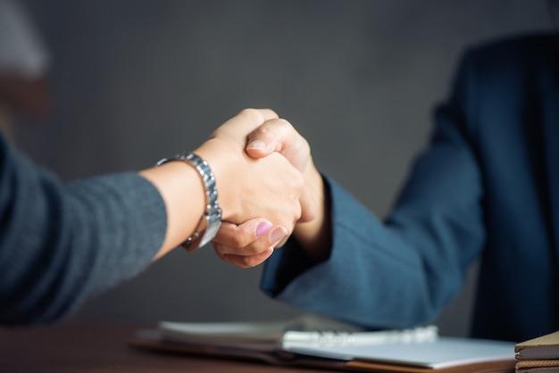 Negoziare le imprese, imprenditrice imprenditrice stretta di mano, felice con il lavoro, donna d'affari che sta godendo con il suo compagno di lavoro, handshake gesturing people concept connection deal. immagini di stile d'effetto vintage. Foto Gratuite
