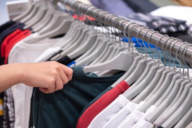 Negozio di abbigliamento, vestiti appesi su una mensola Foto Premium